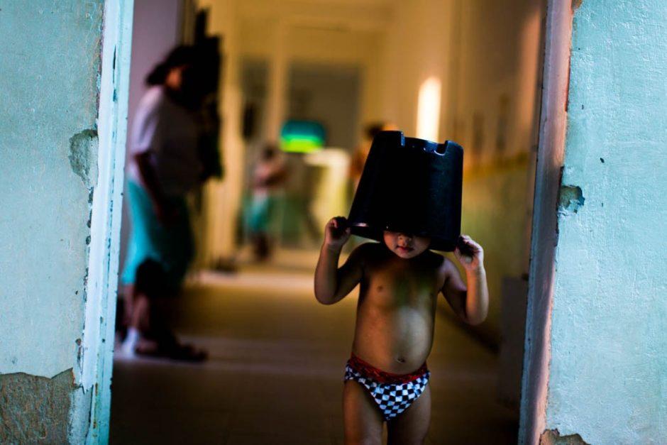 Foto de um garoto com um balde na cabeça em frente de uma porta de um corredor, pessoas caminham neste corredor.