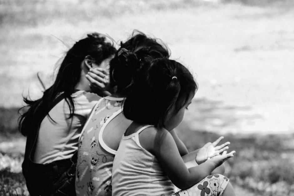 Foto em preto e branco de três meninas sentadas de costas