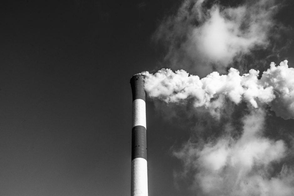 Foto em preto e branco de chaminé de fábrica industrial soltando uma fumaça branca